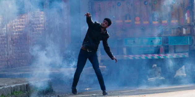 A Kashmiri Muslim protester throws back an exploded tear gas shell at Indian policemen during a protest...