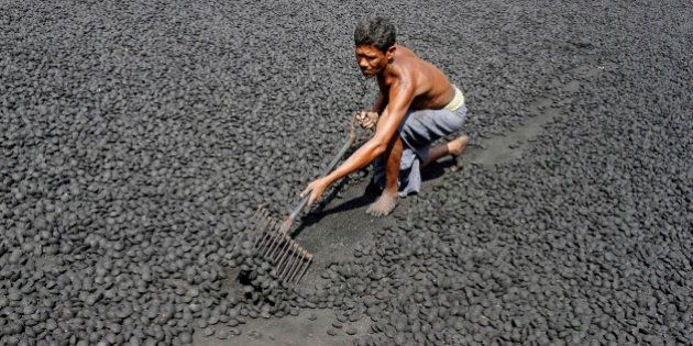 An Indian laborer works at a gol coal factory, where coal is made from its fine powdered form, in the...