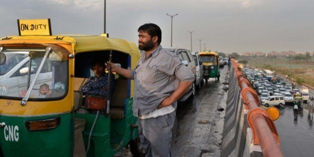 NEW DELHI, INDIA - MARCH 11: An auto rickshaw driver waits as he was stuck in huge traffic Jam due to...