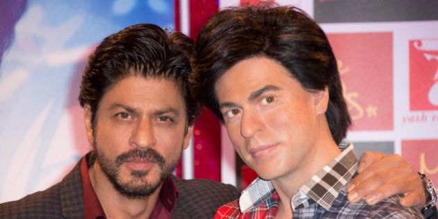 Actor Shah Rukh Khan, left, poses for photographers with his Madame Tussauds wax figure in central London...