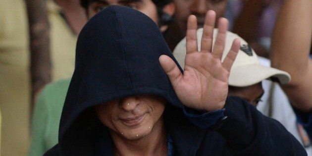 Bollywood actor Shah Rukh Khan, face covered in a hood, waves towards fans as he leaves after finishing...