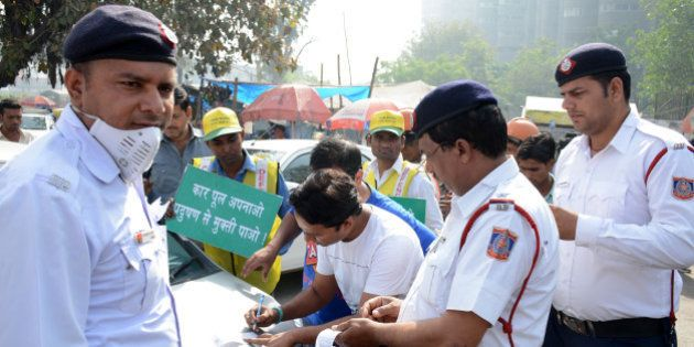 GHAZIABAD, INDIA - APRIL 15: Traffic policemen issue a challan to a commuter for driving an even-number...