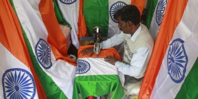 A tailor makes Indian national flags ahead of the Republic Day celebrations in Agartala, India, January...