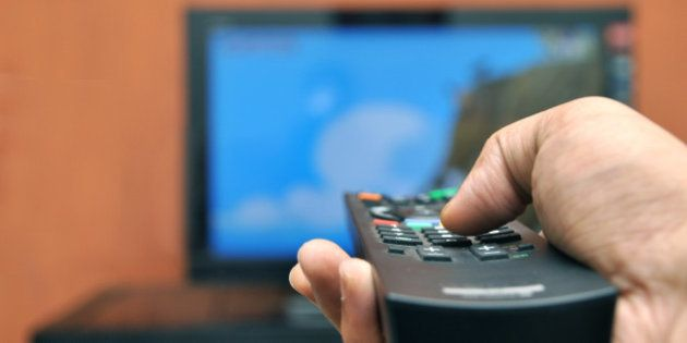 A man holding a TV remote