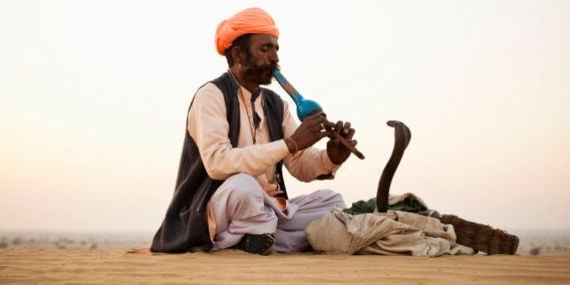 Indian Snake Charmer playing music for Cobra in