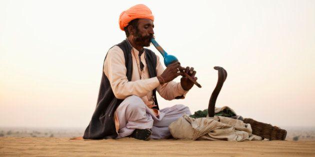 Indian Snake Charmer playing music for Cobra in Desert