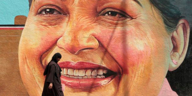 A woman walks past a portrait of J. Jayalalithaa, Chief Minister of the southern Indian state of Tamil...
