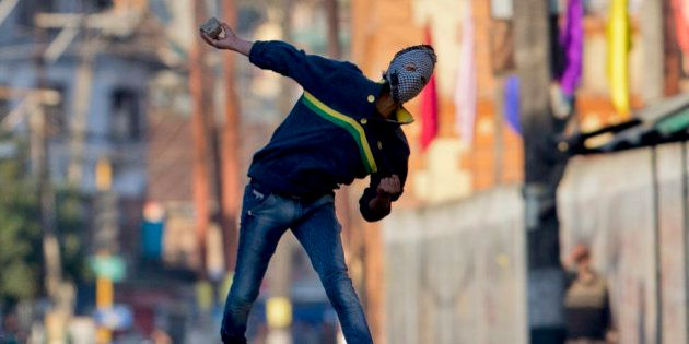 A Kashmiri masked Muslim protester throws rocks at Indian policemen during a protest in Srinagar, Indian...