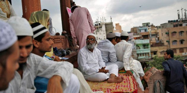 Muslims sit inside the compound of Jama Masjid (Grand Mosque) before the start of last Friday prayers...