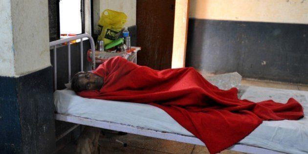 An Indian tuberculosis patient rests while a stray dog drinks water from his mug underneath his bed at...