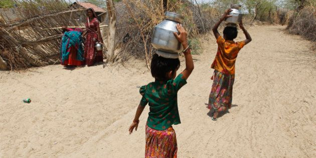 Village girls carry metal pitchers filled with water supplied by the government in the western Indian...