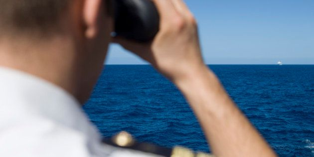 Officer looks through binoculars with cruise ship in distance, near Mozambique, Indian