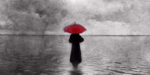 Atmospheric solitary woman with red umbrella wading in
