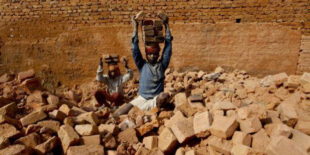 LALITPUR, January 11, 2016 : Indian seasonal migrant laborers carry raw bricks at a brick factory in...