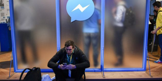 An attendee sits in front of a messenger logo during the Facebook F8 Developers Conference in San Francisco,...