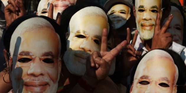 Bharatiya Janata Party (BJP) activists, clad in masks of BJP prime ministerial candidate and Gujarat...