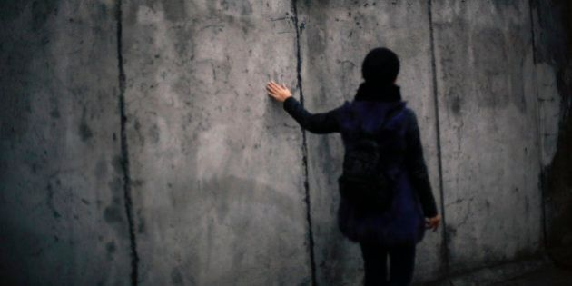 In this photo Oct. 26, 2014 photo a woman touches the wall as she walks alongside the remains of the...