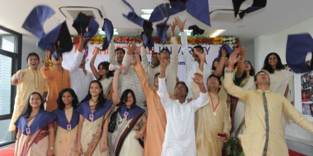 Ahmedabad University students throw their hats into the air as they celebrate their qualifications at...