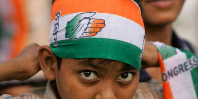 A young supporter of India's ruling Congress party wears a scarf with party symbol, during an election...