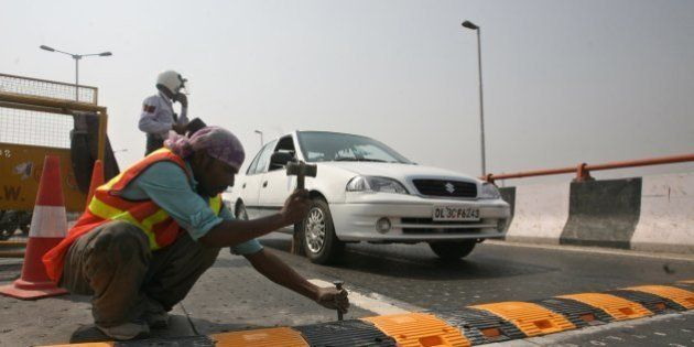 NEW DELHI, INDIA � AUGUST 1: Workers install a metallic speed breaker on the Dwarka flyover after 9...