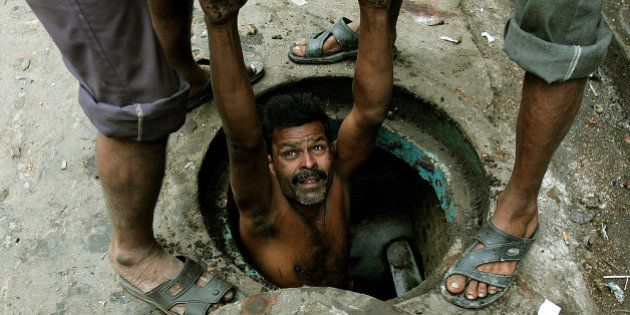 An Indian labourer is lowered to clean a sewage hole in the eastern Indian city of Kolkata December 16,...