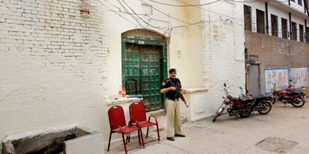 In this Monday, April 25, 2016 photo, a Pakistani policeman stands guard outside the 300-year-old gurdwara...