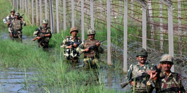 Indian Border Security Force (BSF) soldiers patrol the fenced border with Pakistan as they wade through...