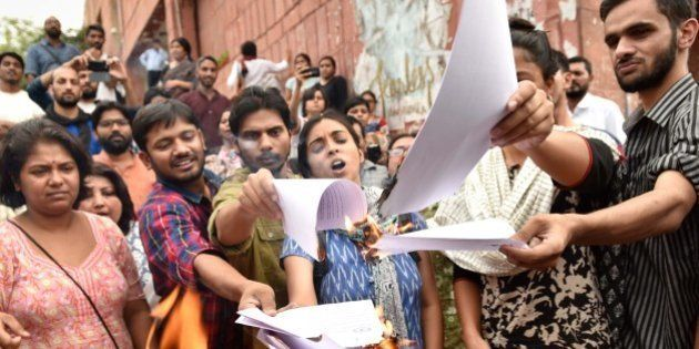 NEW DELHI , INDIA - APRIL 26: JNUSU President Kanhaiya Kumar with Umar Khalid, Anirban Bhattacharya and Shehla Rashid Shora burning copies of the report in front of the administrative block, on April 26, 2016 in New Delhi , India. JNU has suspended students Umar Khalid, Anirban Bhattacharya and Shehla Rashid Shora while slapping a fine of Rs. 10,000 on Students' Union President Kanhaiya Kumar. JNU students' union has decided to go on an indefinite hunger strike starting Wednesday to protest the action taken against its President Kanhaiya Kumar. Kanhaiya, Umar Khalid and Anirban Bhattacharya were arrested on charges of sedition in February in connection with an event against hanging of Parliament attack convict Afzal Guru. (Photo by Vipin Kumar/Hindustan Times via Getty Images)