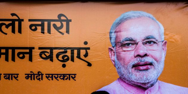 A pedestrian walks past a billboard for the Bharatiya Janta Party (BJP) picturing its prime ministerial...