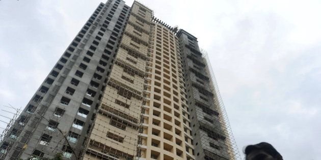 A local resident walks past the controversial Adarsh Housing Society apartments in Mumbai on November...