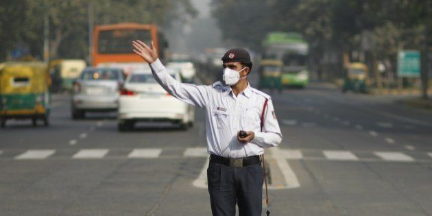 NEW DELHI, INDIA - DECEMBER 9: A traffic policeman wears anti-pollution mask while directing traffic...