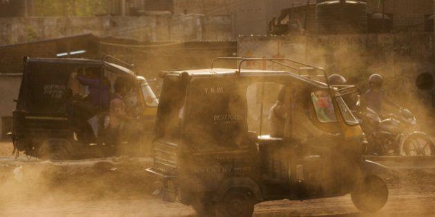 Auto-rickshaws kick up dust as they travel near the Delhi city boundary in Faridabad, Haryana, India,...