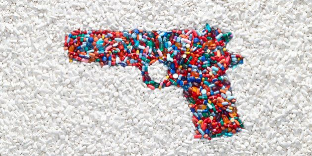 A handgun formed by colored pills surrounded by white