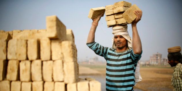 An Indian migrant worker stack bricks on his head at a brick factory in Lalitpur, Nepal January 11, 2016....