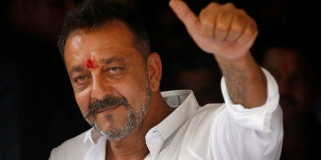 Bollywood actor Sanjay Dutt shows a thumbs up sign after arriving at his residence in Mumbai, India,...