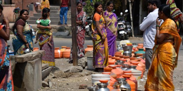 LATUR, INDIA - MARCH 23: People lined up with their pots to collect drinking water from government boring...