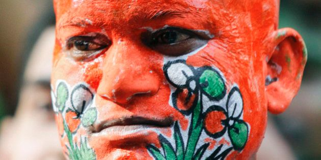 A supporter of the Trinamool Congress with his body painted in the colours of the party, celebrates on...