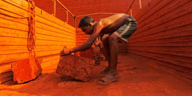 Sunil, 14, loads a brick onto the back of a truck at a laterite brick mine in Ratnagiri district, about...