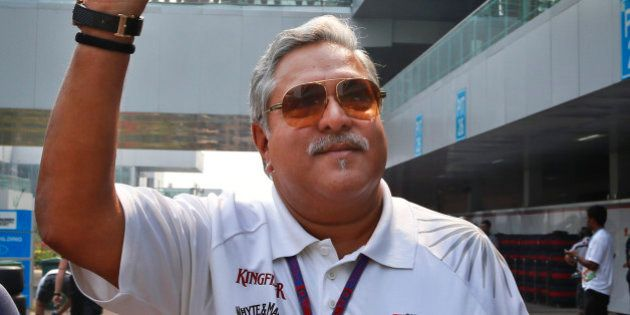 Force India team principal and businessman Vijay Mallya waves as he walks down the F1 paddock after the...