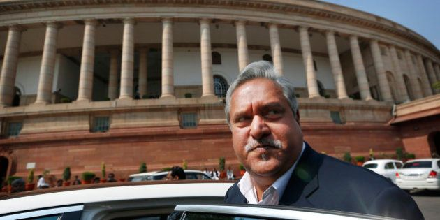 Indian business tycoon and owner of Kingfisher Airlines Vijay Mallya gets into his car outside Parliament...