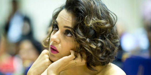 Indian actress Kangana Ranaut listens to a speaker before receiving her national award for best actress...
