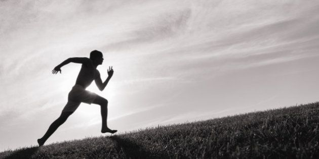 Silhouette of young man running up a