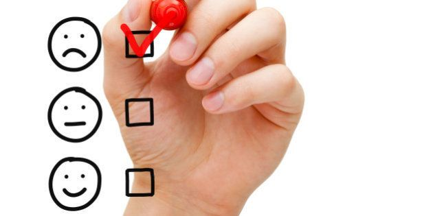 Hand putting check mark with red marker on poor customer service evaluation