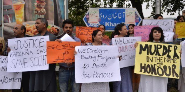 Pakistani human rights activists hold placards as they chant slogans during a protest in Islamabad on...