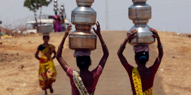 Indian women walk home after collecting drinking water from a well at Mengal Pada in Thane district in...