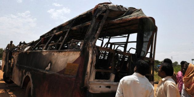 Villagers inspect a burnt-out passenger bus of the Karnataka State Road Transport Corporation (KSRTC)...
