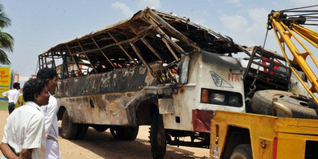 Villagers look on as a burnt-out passenger bus of the Karnataka State Road Transport Corporation (KSRTC)...