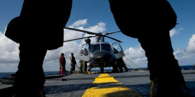A Philippine Navy personnel stands in front of an AgustaWestland AW109 helicopter before it takes off...