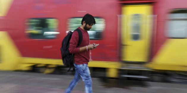 A passenger walks past a train while using a smartphone at Mumbai Central railway station in Mumbai,...
