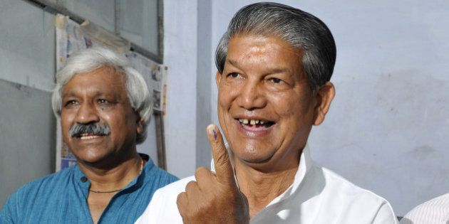 DEHRADUN, INDIA - MAY 7: Uttrakhand Chief Minister Harish Rawat showing ink stained finger after casting...